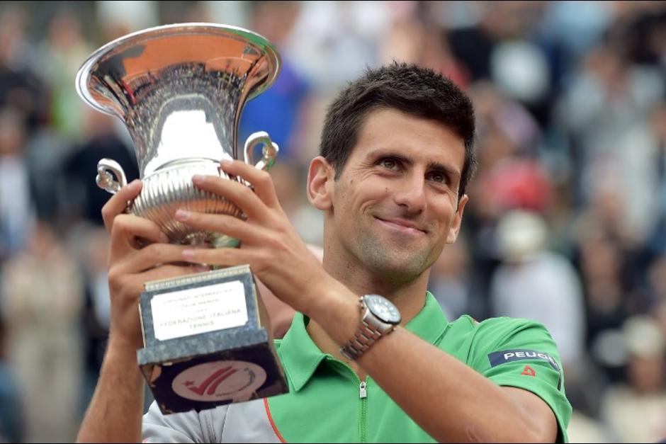 Novak Djokovic of Serbia holds the trophy after winning his ATP Rome's Tennis Masters final against Rafael Nadal of Spain on May 18, 2014, at the Foro Italico in Rome. Djokovic won 4-6, 6-3, 6-3.  AFP PHOTO / GABRIEL BOUYS